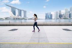 Asiatisk kvinna som joggar på promenadbron Arkivbild