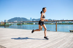 Asiatisk kvinna som joggar på strandpromenaden Arkivbild