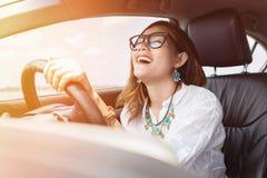 Asiatisk kvinna som kör en bil Arkivbild