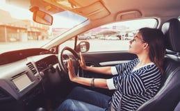 Asiatisk kvinna som kör en bil Arkivfoto
