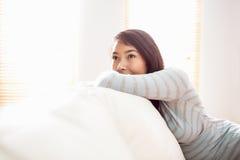 Asiatisk kvinna som kopplar av på soffan Royaltyfri Fotografi