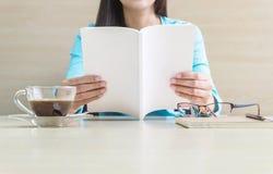 Asiatisk kvinna som läser en vit bok i hennes fria tid i rummet med den träskrivbordet och väggen under fönsterljus, avkoppling a Arkivbild