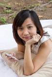 Asiatisk kvinna som ler med den mobila telefonen på parken Arkivbilder