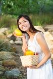 Asiatisk kvinna som ler med en mango och en korg av spanska peppar och mango Fotografering för Bildbyråer