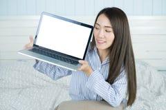 Asiatisk kvinna som ler och visar den tomma bärbar datordatorskärmen i hennes sovrum Royaltyfria Bilder