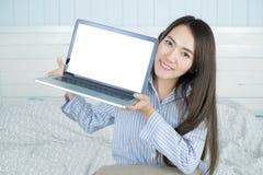 Asiatisk kvinna som ler och visar den tomma bärbar datordatorskärmen i hennes sovrum Fotografering för Bildbyråer