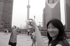 Asiatisk kvinna som ler på det pärlemorfärg tornet arkivbild