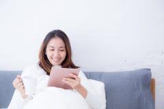 Asiatisk kvinna som ligger i sovrum med digitalt minnestavla- och drinkkaffe royaltyfri bild