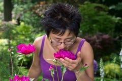 Asiatisk kvinna som luktar blomman arkivbild