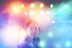 Asiatisk kvinna som lyssnar till musik i hörlurar arkivbilder