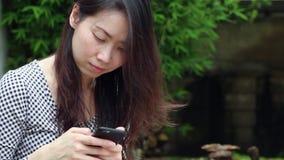 Asiatisk kvinna som pratar på telefonen i trädgården stock video