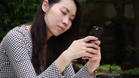 Asiatisk kvinna som pratar på telefonen i trädgården lager videofilmer