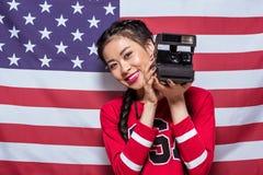 Asiatisk kvinna som rymmer den retro fotokameran med amerikanska flaggan bakom Royaltyfri Bild