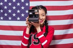 Asiatisk kvinna som rymmer den retro fotokameran med amerikanska flaggan bakom arkivfoto