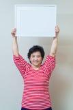 Asiatisk kvinna som rymmer den tomma vita bildramen i studioskottet, sp Arkivfoto