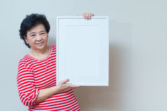 Asiatisk kvinna som rymmer den tomma vita bildramen i studioskottet, sp Royaltyfri Fotografi