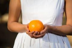 Asiatisk kvinna som rymmer en apelsin Fotografering för Bildbyråer