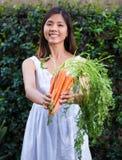 Asiatisk kvinna som rymmer en grupp av morötter Arkivfoto