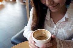 Asiatisk kvinna som rymmer en kaffekopp, innan att dricka med mening bra i kafé arkivfoto