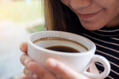 Asiatisk kvinna som rymmer en kaffekopp, innan att dricka med mening bra i kafé arkivfoton