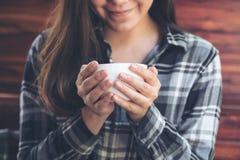 Asiatisk kvinna som rymmer en kaffekopp, innan att dricka med mening bra i kafé royaltyfri bild