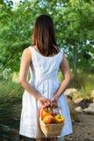 Asiatisk kvinna som rymmer en korg av spanska peppar och mango Arkivfoto