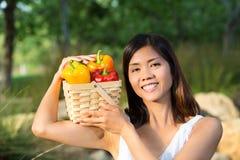 Asiatisk kvinna som rymmer en korg av spanska peppar och mango Royaltyfri Foto