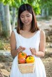 Asiatisk kvinna som rymmer en korg av spanska peppar och mango Arkivfoton