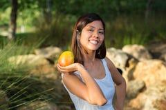Asiatisk kvinna som rymmer en mango Royaltyfria Foton