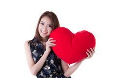 Asiatisk kvinna som rymmer en röd hjärta arkivfoton