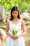 Asiatisk kvinna som rymmer en vit blomma Fotografering för Bildbyråer