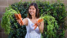 Asiatisk kvinna som rymmer grupper av morötter Royaltyfria Bilder