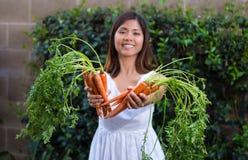 Asiatisk kvinna som rymmer grupper av morötter Arkivfoton