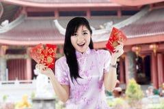 Asiatisk kvinna som rymmer röda kuvert Fotografering för Bildbyråer