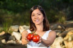 Asiatisk kvinna som rymmer röda tomater Royaltyfri Fotografi