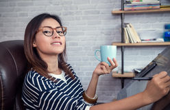 Asiatisk kvinna som ser ner på en kopp Arkivbild