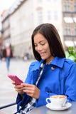 Asiatisk kvinna som smsar på telefonen på det utomhus- kafét fotografering för bildbyråer