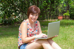 Asiatisk kvinna som spelar bärbara datorn i trädgården Royaltyfri Foto