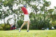 Asiatisk kvinna som spelar den svängande golfklubben för golf för teeing av i kurs arkivbilder
