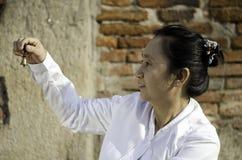 Asiatisk kvinna som spelar en klocka Royaltyfria Bilder