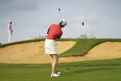 Asiatisk kvinna som spelar golf utomhus i kurs i sommar Arkivfoton