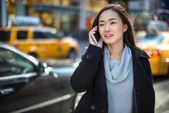 Asiatisk kvinna som talar på mobiltelefonen Arkivfoto