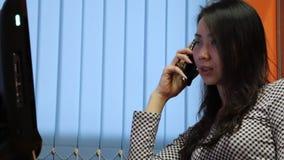 Asiatisk kvinna som talar på telefonen i kontoret lager videofilmer