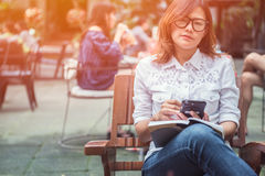 Asiatisk kvinna som tar anmärkningar på telefonen Fotografering för Bildbyråer