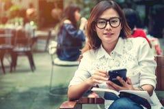 Asiatisk kvinna som tar anmärkningar på telefonen Arkivbilder