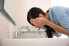 Asiatisk kvinna som tvättar hennes framsida på vasken Royaltyfri Bild