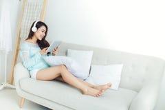 Asiatisk kvinna som tycker om att sitta på soffan och att lyssna till musik arkivbilder