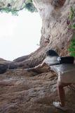 Asiatisk kvinna som upp klättrar repet på den steniga klippan Royaltyfria Bilder
