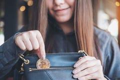 Asiatisk kvinna som upp väljer och tappar bitcoin in i en svart plånbok royaltyfri bild