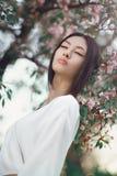 Asiatisk kvinna utomhus på våren mot blommablomningen royaltyfri bild